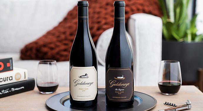 Goldeneye Pinot Noir bottles on a table with two wine glasses