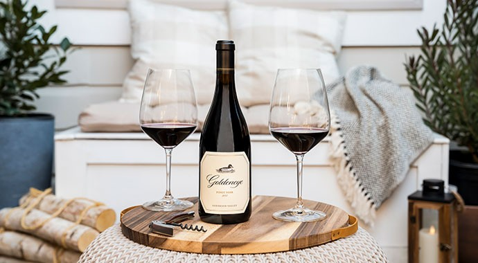 Goldeneye Pinot Noir on the porch with two wine glasses