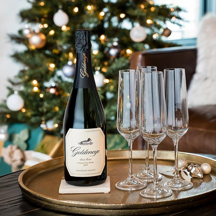 Goldeneye Sparkling on a tray with glasses in front of a Christmas tree
