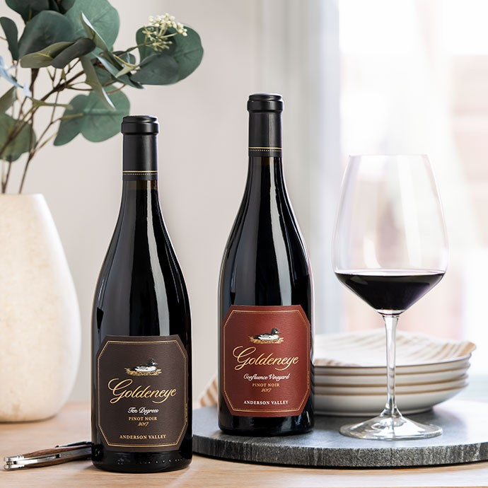 Goldeneye Pinot Noir with a glass of wine and plates