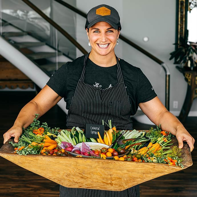 Chef Natalie Niksa of La Saison holding a platter of food